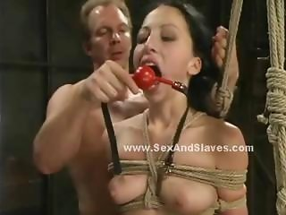 Blonde tied on wall of pain with huge breasts naked and pussy filled with a toy gives rough blowjob