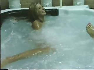 Two lesbians play with a dildo in a jacuzzi