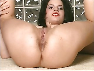 Black haired girl wearing red lipstick spreads her pussy