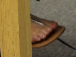 Brunette college girl feet dangling sandals in library